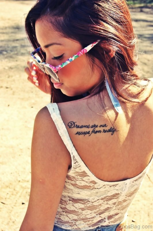 Dreams Quote Tattoo on a Women's Shoulder