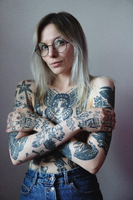 Tattooed Woman with glasses and crossed arms